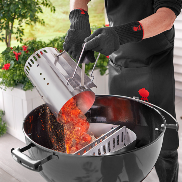 Wearing protective clothing or gloves, carefully pour the glowing briquettes into your barbecue (this barbecue is using Weber Char-Baskets)