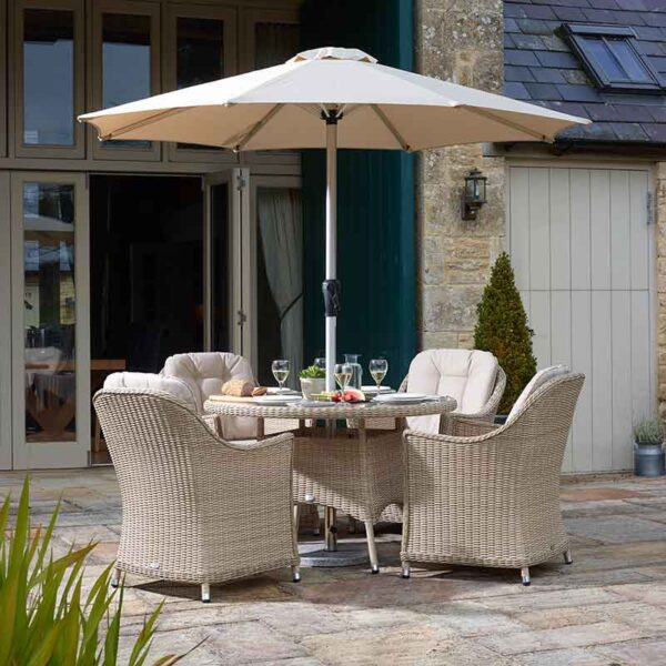 Bramblecrest Monterey 4 Seater Dining Set in Sandstone with Parasol & Base on patio