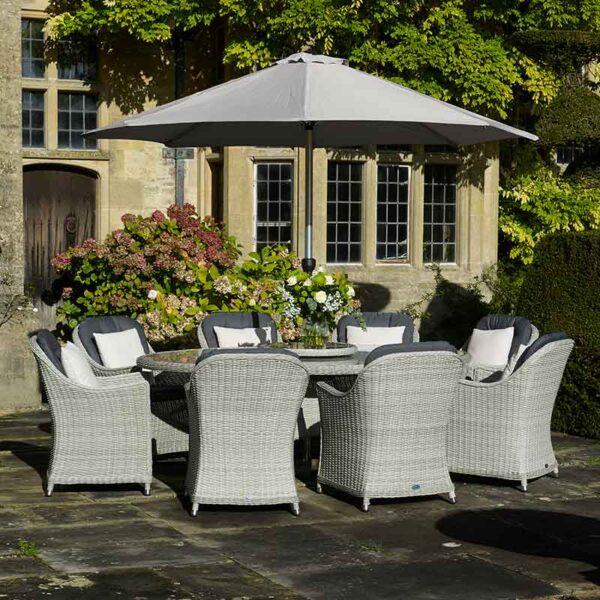 Bramblecrest Monterey 8 Seat Oval Dining Set with Lazy Susan, Parasol & Base on patio