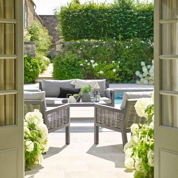 Bramblecrest Portofino 4 Seater Aluminium & Wicker Outdoor Lounge Set on patio