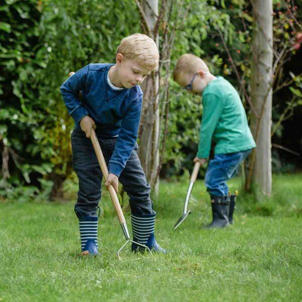 Child using the Kent & Stowe Kids Stainless Steel Garden Rake