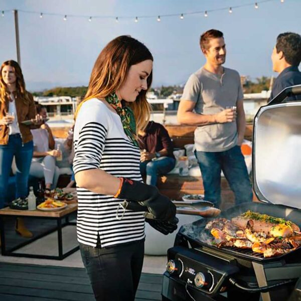 Weber Pulse 2000 Electric Barbecue with Stand in use at Rooftop Party