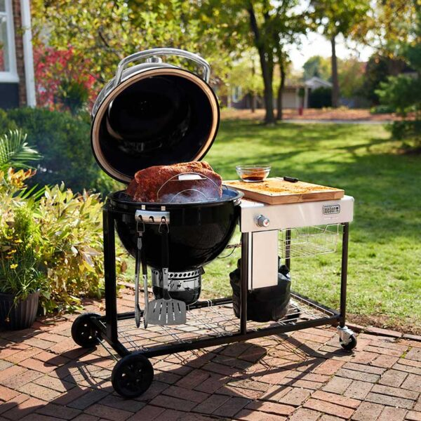 Weber Summit Kamado S6 Charcoal Grill Centre with the lid open in garden
