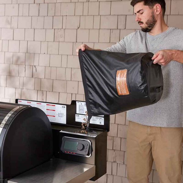 Wood pellets pour in easily with the Weber Fuel Storage Bag